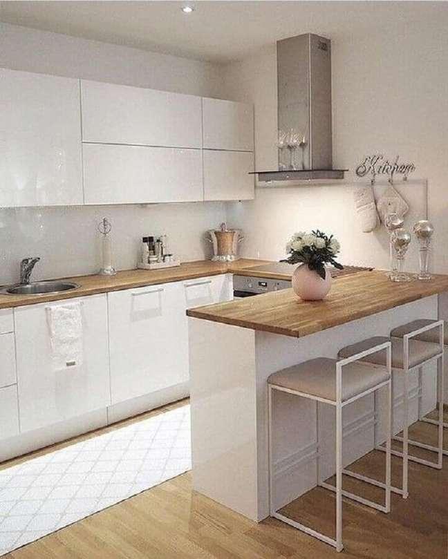 37. Decoração de cozinha estilo americana branca com bancada de madeira em U – Foto: Pinterest
