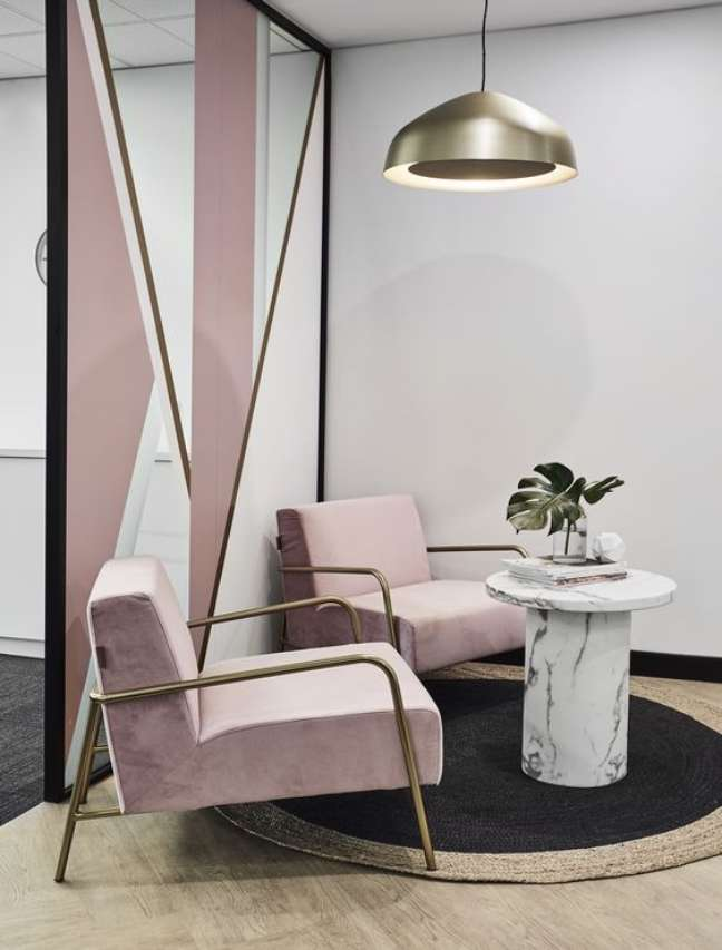 55. Sala de espera com poltronas cor de rosa e mesa de centro marmorizada com revistas e vaso de plantas – Foto Morphos Projects