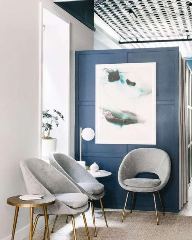 13. Sala de espera moderna com cadeiras cinza e parede azul – Foto The Venue Report