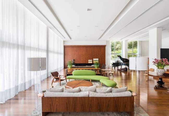 83. Sala grande decorada com criatividade e sofá verde e móveis de madeira – Projeto Leonardo Muller
