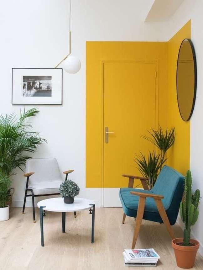 47. Parede de sala decorada com pintura setorizada em amarelo – Foto Iaza