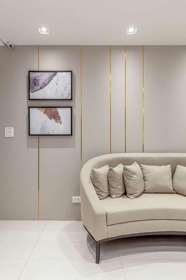 61. Sala de espera chique com sofá redondo bege e papel de parede dourado -Foto RPGuimarães