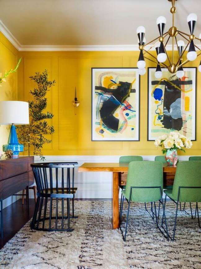77. Sala de jantar grande decorada com tons de amarelo com cadeira retrô verde – Foto Casoca