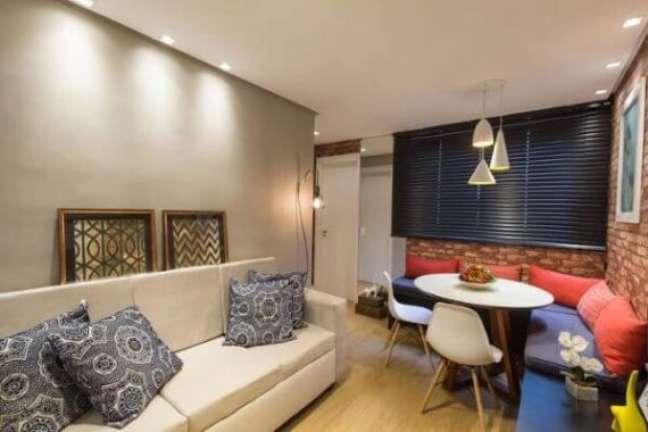 19. Parede decorada para sala com cimento queimado e quadros apoiados no sofa – Foto Andrea Fonseca