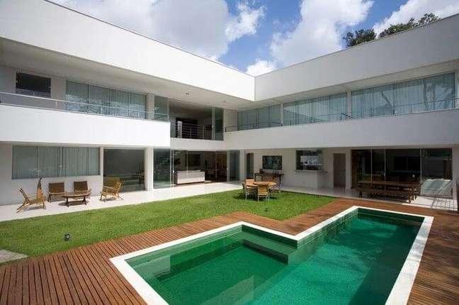 44. Portas de correr de vidro e piscina verde esmeralda decoram a área externa. Projeto de Ricardo Abreu Arquitetos