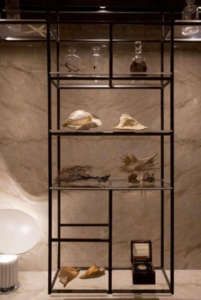 26. A estante de vidro pode ser usada em diferentes cômodos do imóvel. Projeto de Sandra Moura