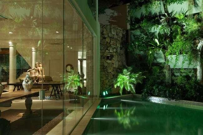 24. A iluminação noturna realça o azulejo de piscina verde. Projeto de Di Pace e Di Pace Arquitetura e Interiores