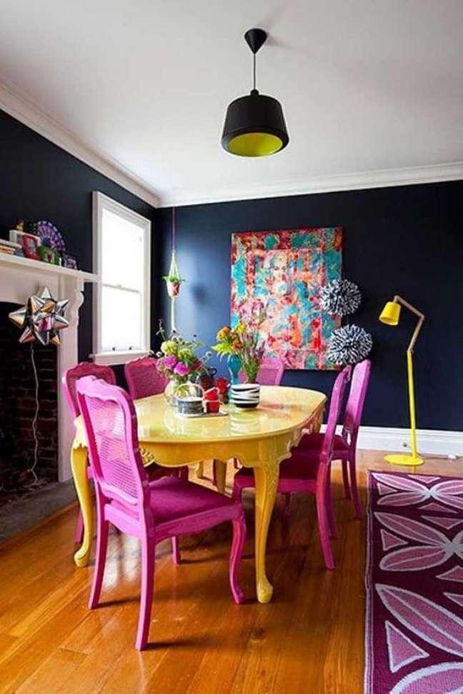15. Parede de sala decorada na cor azul marinho com quadro colorido e móveis nas mesmas tonalidades – Foto Minha Casa Minha Cara