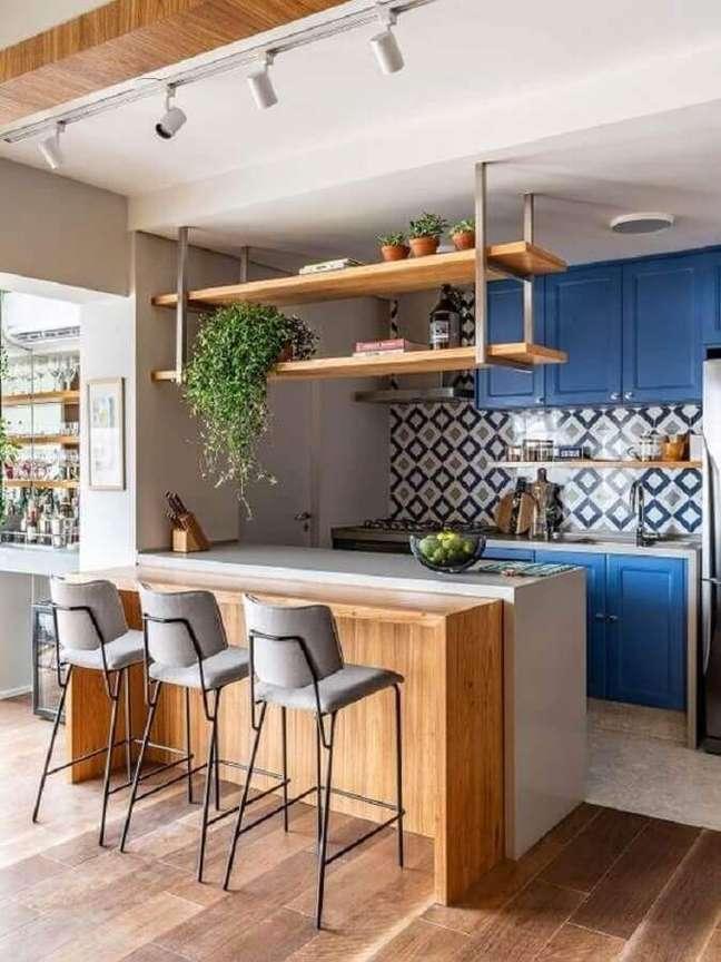 11. Armário azul para decoração de cozinha estilo americana planejada com bancada e prateleira de madeira – Foto: Pinterest
