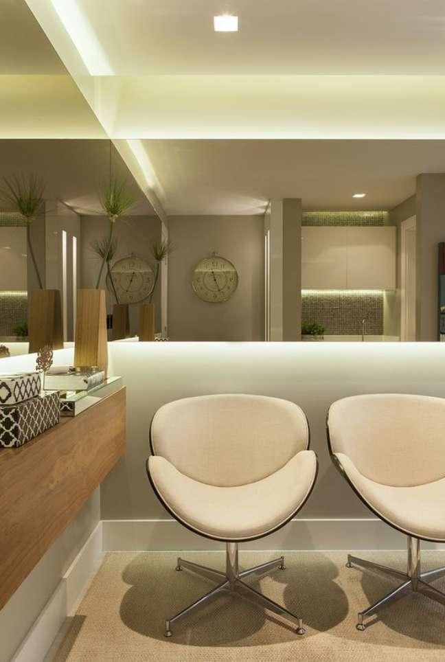 52. Sala de espera com poltronas brancas e espelho ao redor do espaço – Foto Casa Casada