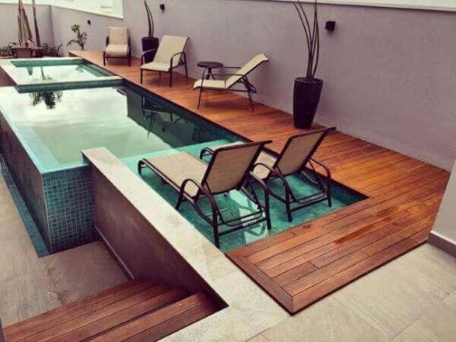 43. Piscina verde elevada com deck de madeira e espreguiçadeira. Fonte: Pinterest