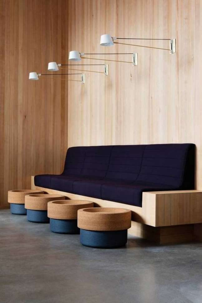 60. Sala de espera com sofá azul marinho e estrutura de madeira – Foto Domino Magazine