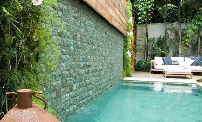 41. Piscina com azulejo verde e jardim vertical decoram a área externa do imóvel. Projeto de André Arquimagens