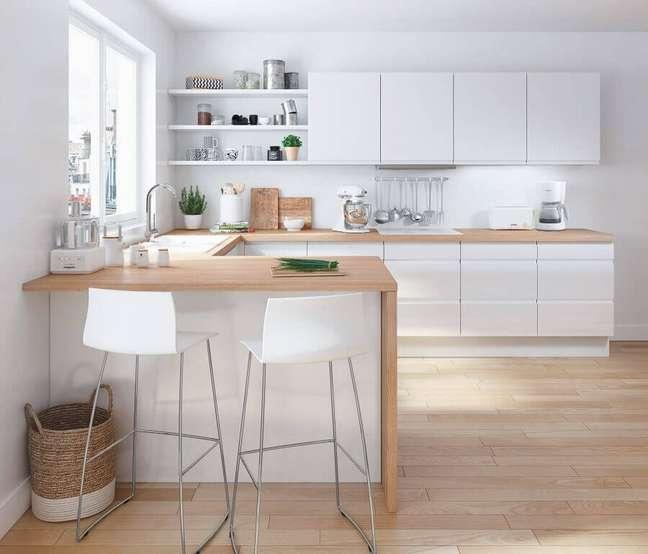 7. Decoração clean para cozinha estilo americana branca em U com bancada de madeira clara – Foto: Pinterest