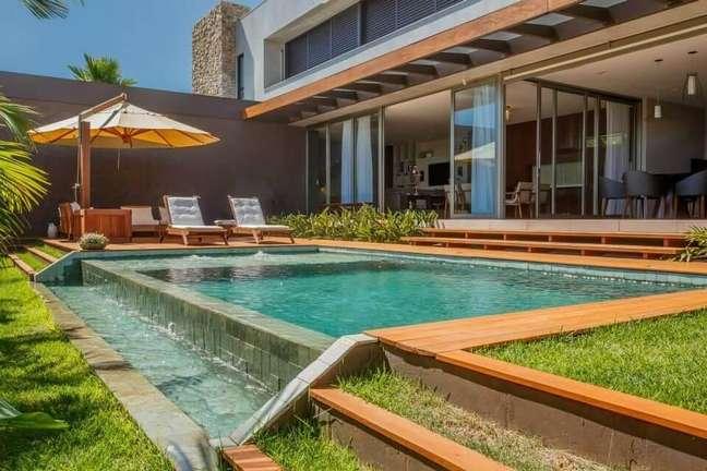 25. Espreguiçadeiras de madeira e ombrelone trazem conforto para aqueles que apreciam a piscina pastilha verde. Projeto de WT Studio