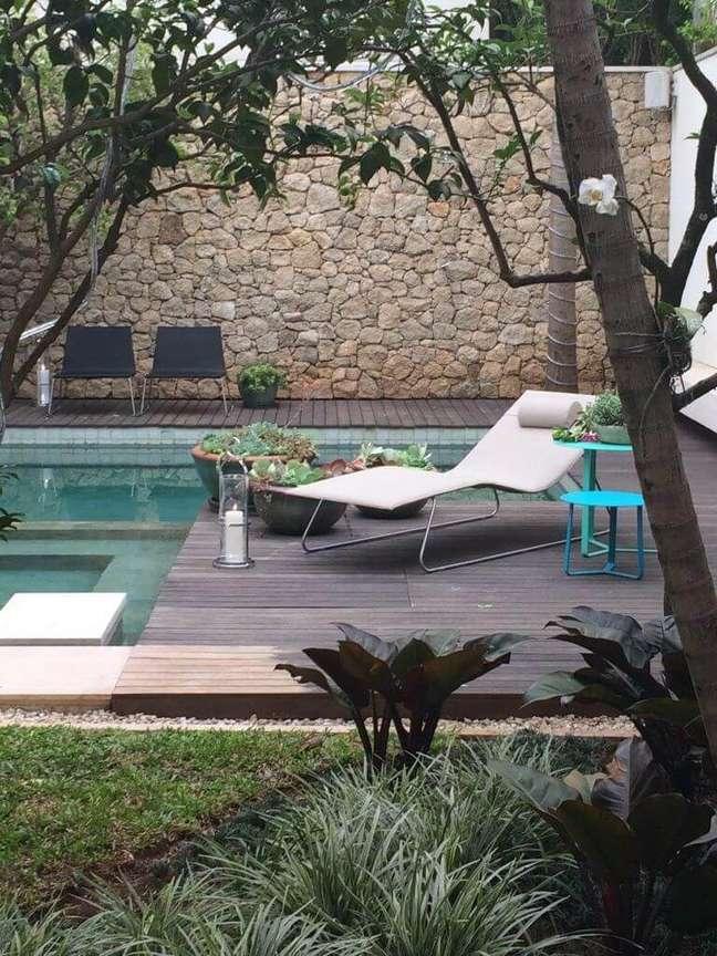 30. Muro revestido com pedras e piscina com azulejo verde. Projeto de Catê Poli Paisagismo