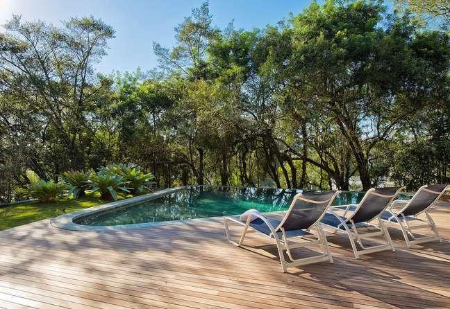 38. O revestimento verde para piscina com borda infinita se mistura com a vegetação. Projeto de Leonardo Muller