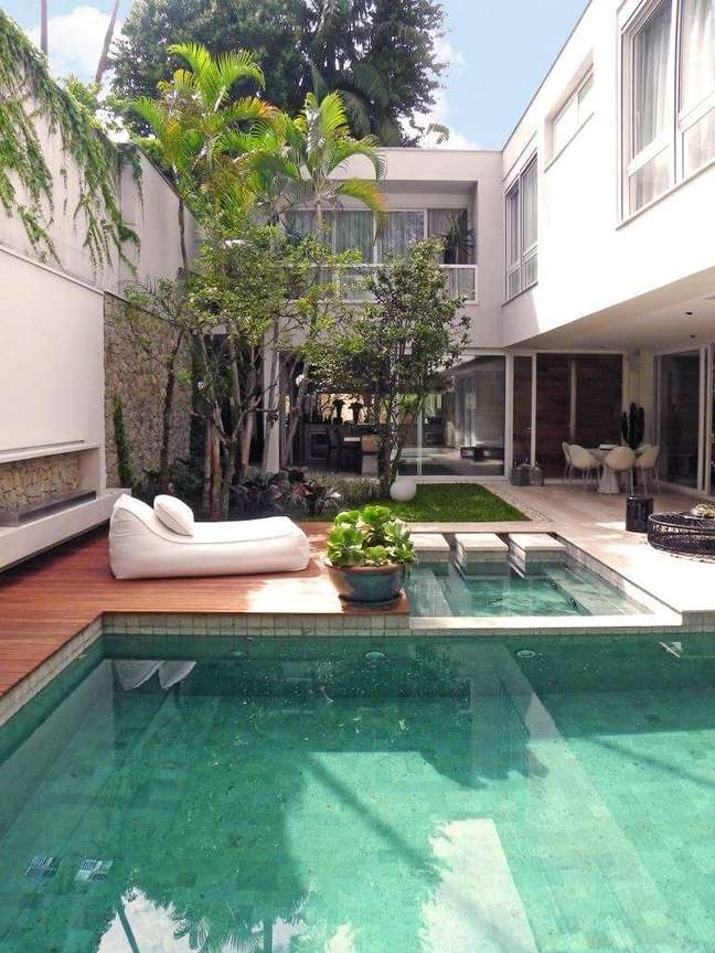 1. Deck de madeira, puff branco e azulejo de piscina verde decoram a área externa. Projeto de Catê Poli Paisagismo