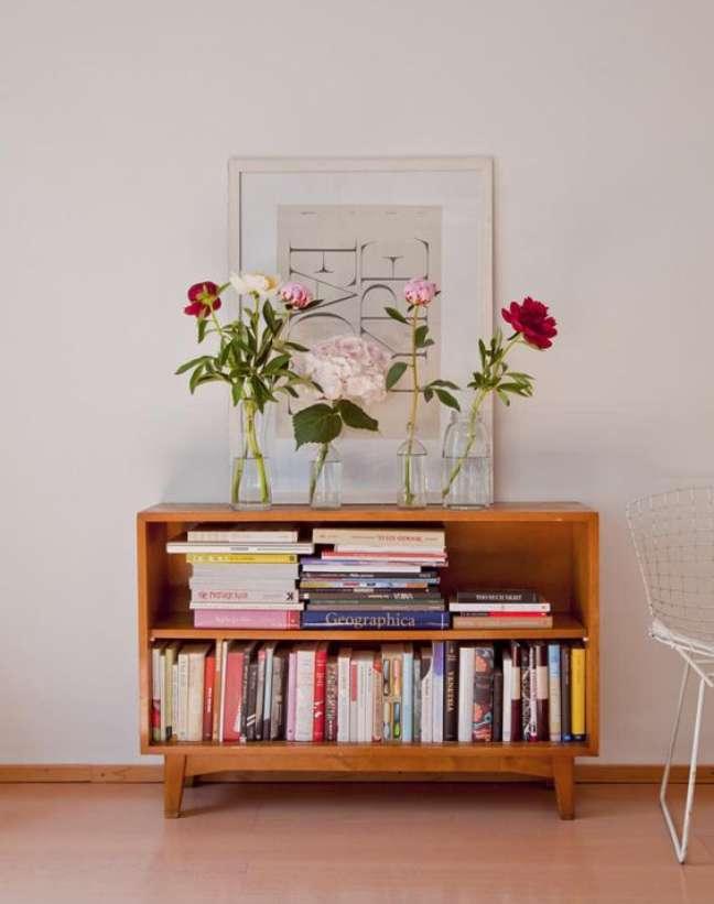 18. Parede de sala pequena decorada com quadros e uma mini estante de livros – Foto casa de Valenitna