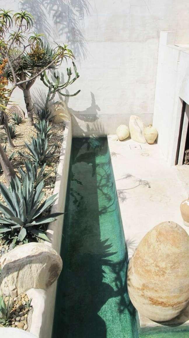 13. A piscina verde se destaca na área de lazer desse imóvel. Fonte: Pinterest