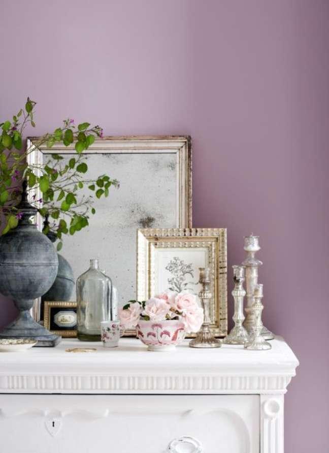 16. Parede de sala decorada na cor lilás com móveis brancos e quadros com moldura dourada – Foto Paintzen