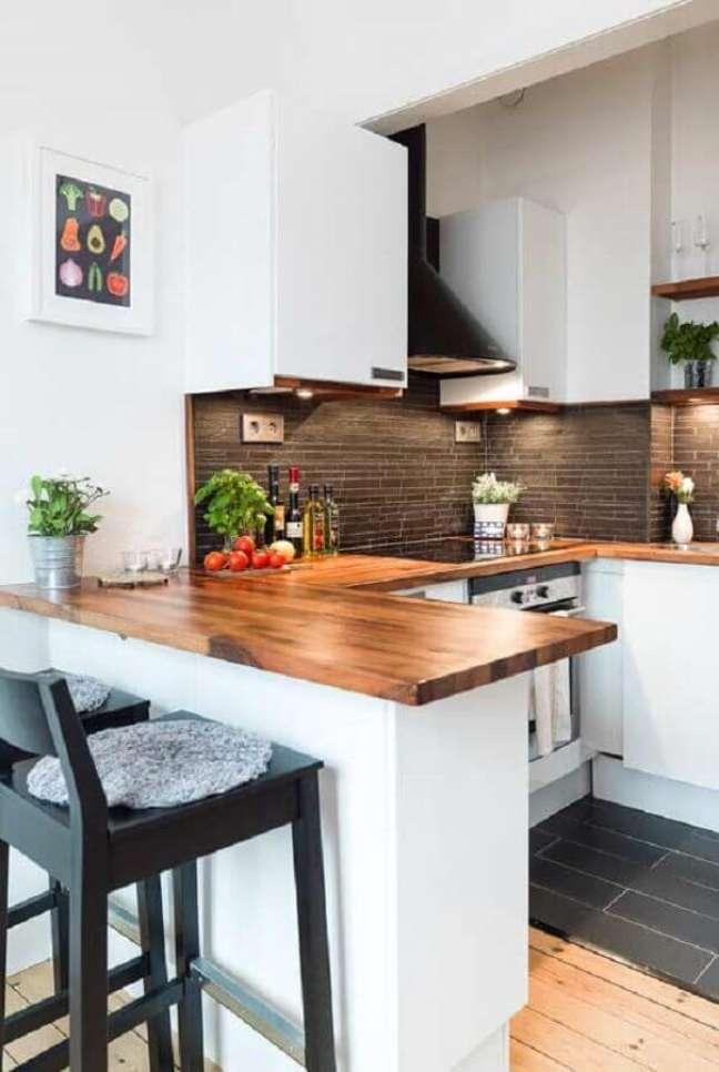 32. Cozinha estilo americana em U decorada com armários brancos e bancada de madeira – Foto: Home Fashion Trend