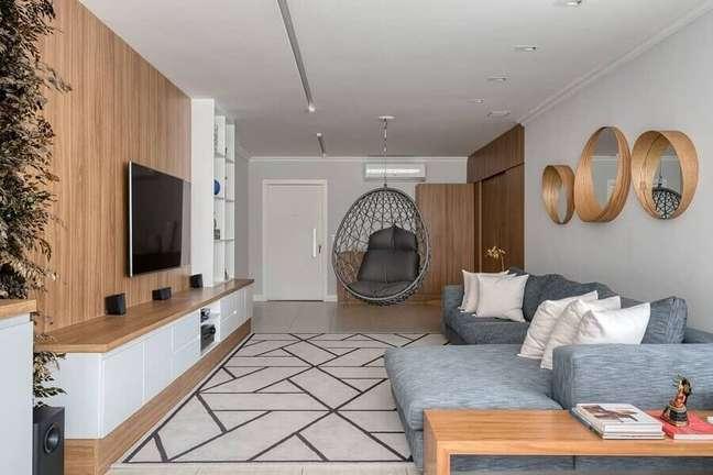 9. Cadeira de balanço moderna suspensa para sala de TV decorada com painel de madeira e sofá cinza – Foto: Flávia e Letícia Abaurre