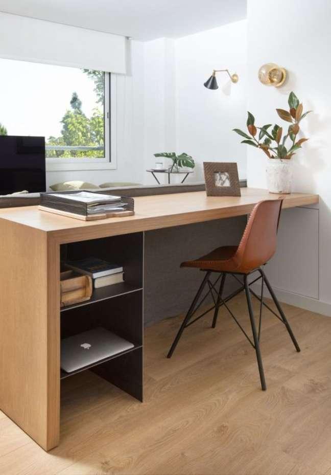 4. Home office na sala com escrivaninha de madeira e cadeira de couro – Foto Editions de Arkhan