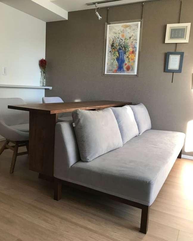 33. Home office na sala com sofá cinza e mesa de escritório de madeira – Foto Pinterest