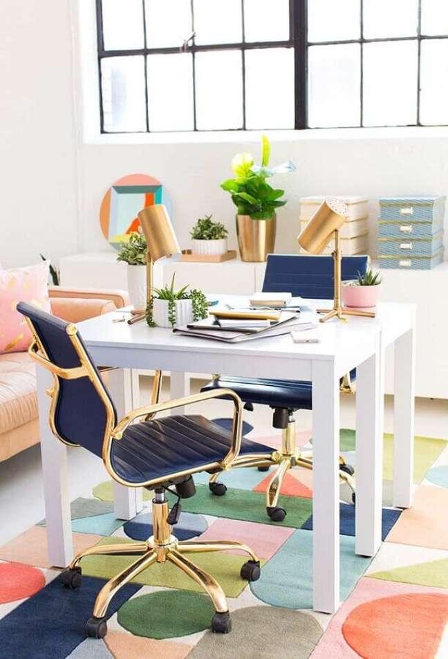 6. Decoração de home office pequeno na sala com cadeiras azuis e douradas – Foto HomeYdeas