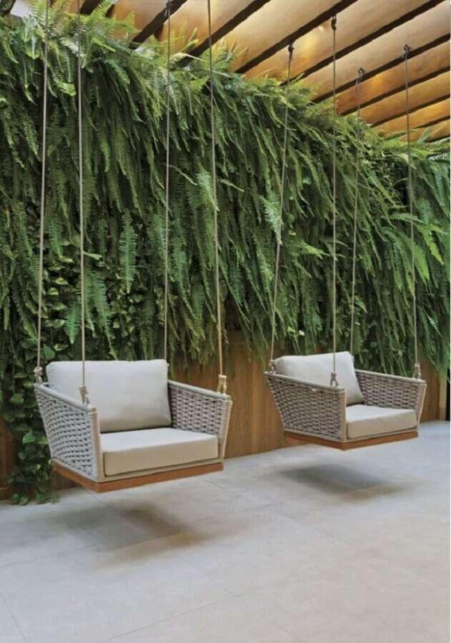 8. Cadeira de balanço moderna suspensa para decoração de varanda com jardim vertical – Foto: Revista InterArq