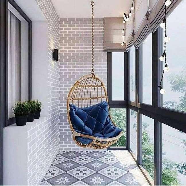 31. Cadeira de balanço suspensa para varanda pequena decorada com piso antigo – Foto: Pinterest