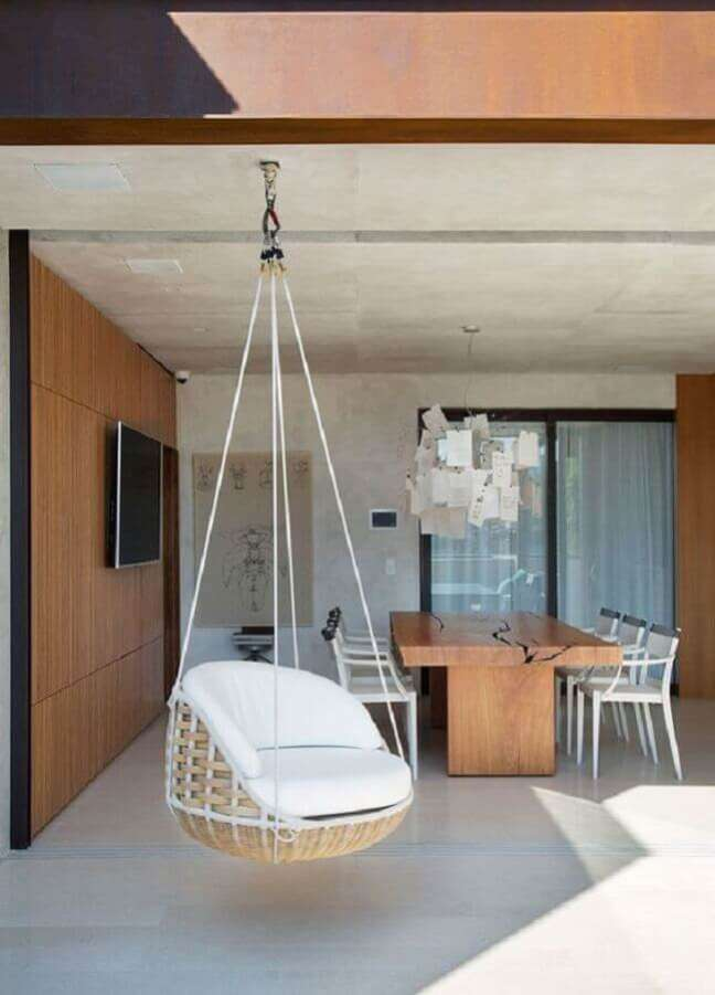 47. Decoração com painel de madeira e cadeira de balanço suspensa para varanda gourmet grande – Foto: Casa de Valentina