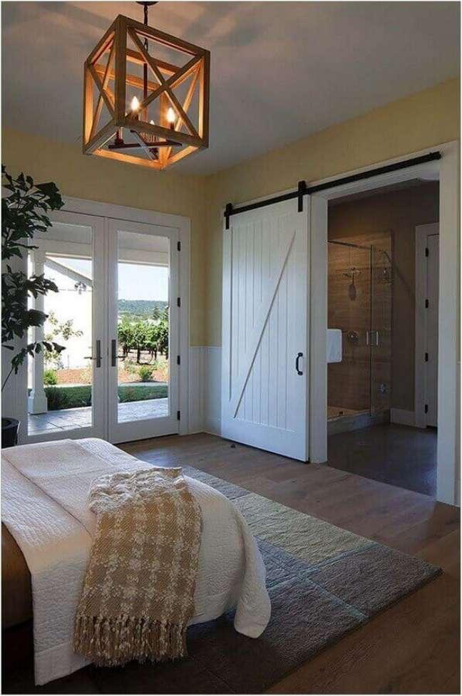 39. Quarto rustico com lustre de madeira quadrado – Foto Apartment Therapy