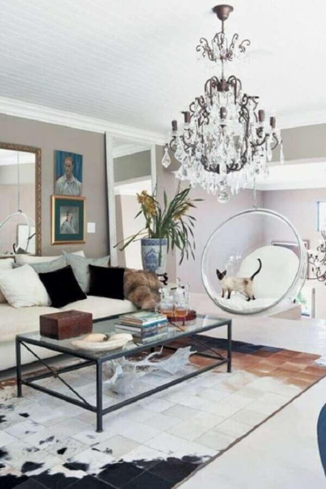 61. Sala de estar decorada com tapete de couro e cadeira de balanço moderna suspensa – Foto: Fashionismo