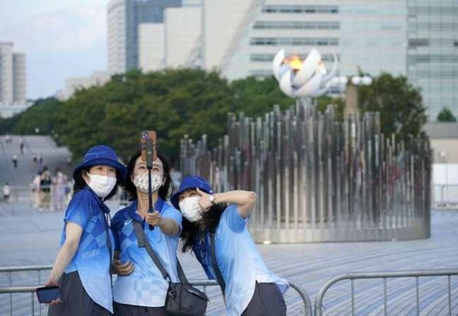 Voluntárias das Olimpíadas fazem selfie com a pira olímpica em Tóquio
