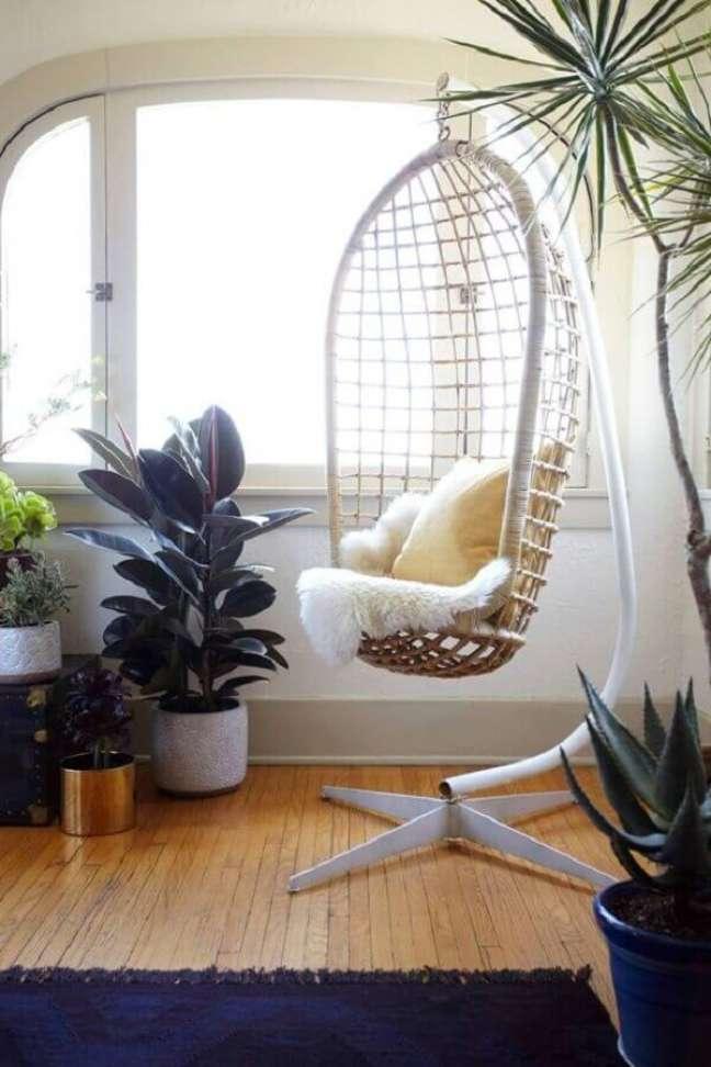 49. Decoração de sala com vasos de plantas e cadeira de balanço suspensa com suporte – Foto: Pinterest