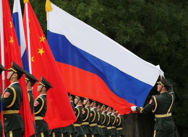 Militares chineses estendem bandeiras de China e Rússia durante solenidade em Pequim  08/06/2018 REUTERS/Jason Lee