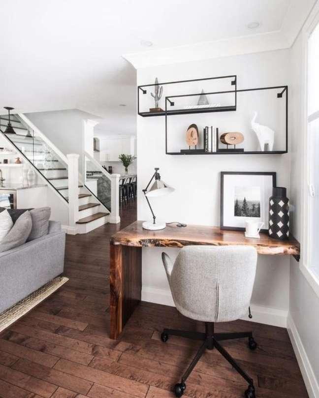 36. Home office na sala de estar com mesa de madeira rustica e cadeira giratoria cinza – Foto Poploly