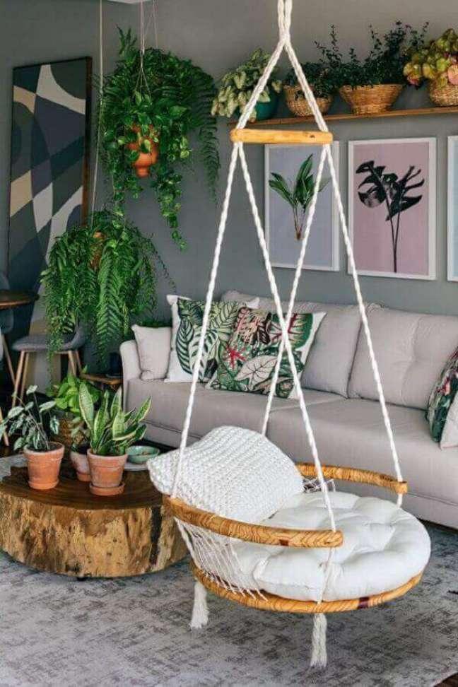 2. Cadeira de balanço suspensa para sala cinza decorada com vasos de plantas e mesa de centro rústica – Foto: Pinterest