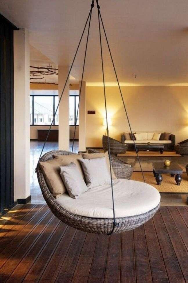27. Cadeira de balanço suspensa para sala grande decorada com piso de madeira – Foto: Côté Maison