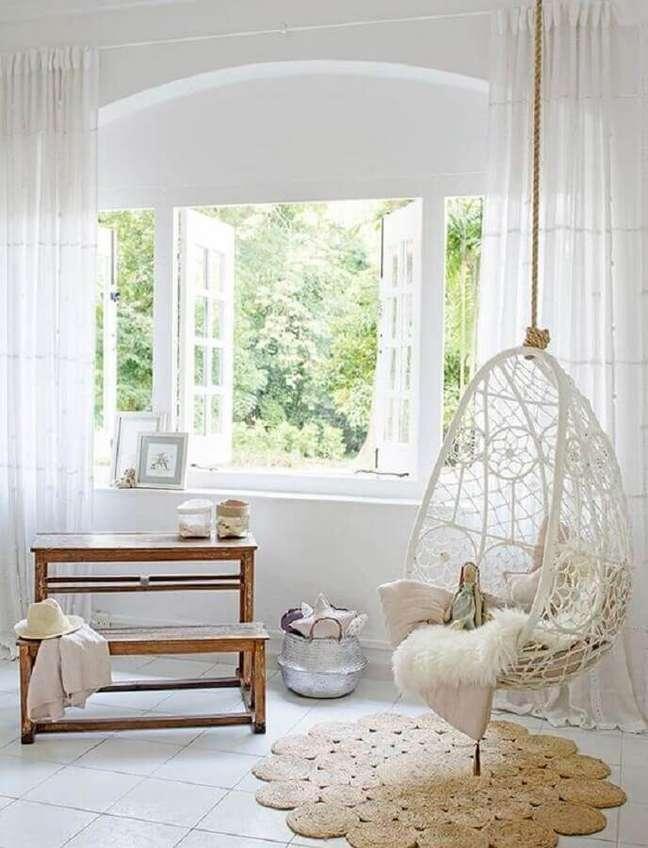 37. Decoração clean para sala branca com cadeira de balanço suspensa – Foto: Sundry Society