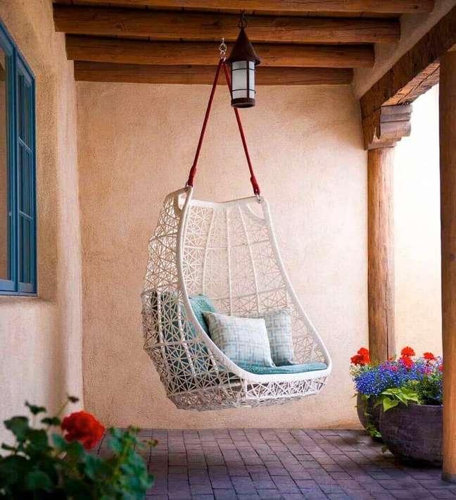32. Cadeira de balanço suspensa para varanda rústica decorada com vasos de chão – Foto: One Kindesign