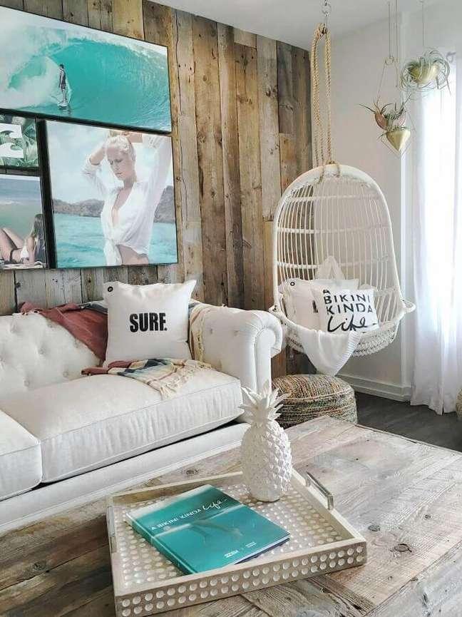 25. Cadeira de balanço suspensa para sala decorada com sofá branco e parede rústica de madeira – Foto: Billabong Women's