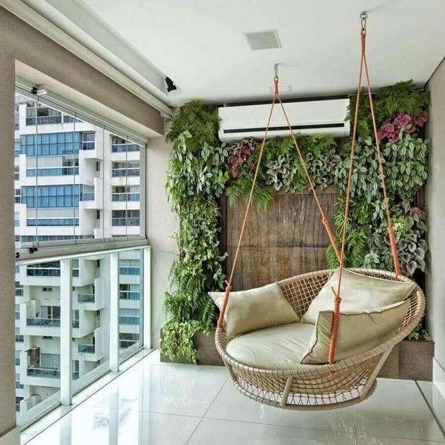 1. Cadeira de balanço suspensa para varanda de apartamento decorada com jardim vertical – Foto: Pinterest