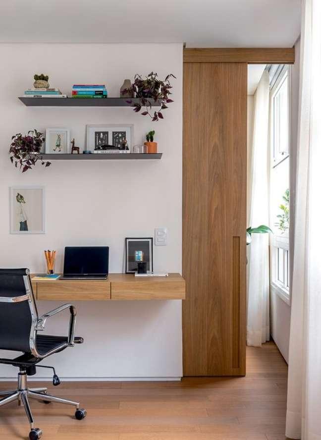 37. Home office na sala de estar moderna feita de madeira e com cadeira confortavel – Foto Revista casa e Jardim