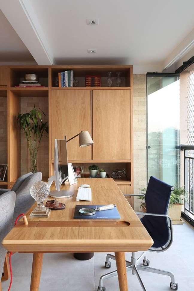 31. Home office na sala com mesa grande de madeira e cadeira giratoria preta – Foto Casa de Valentina