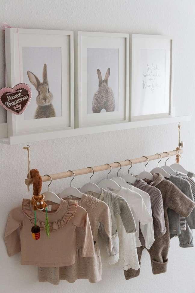 43. Cabideiro simples na prateleira decorada com quadros e cômoda abaixo – Foto Mummy
