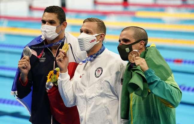 Bruno Fratus exibe a sua medalha de bronze ao lado de Dressel (ouro) e Manadou (prata)