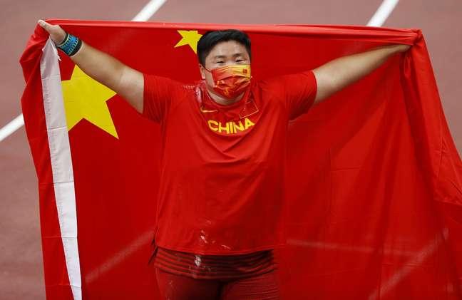 Gong Lijiao of China comemora a medalha de ouro com a bandeira da China Phil Noble Reuters